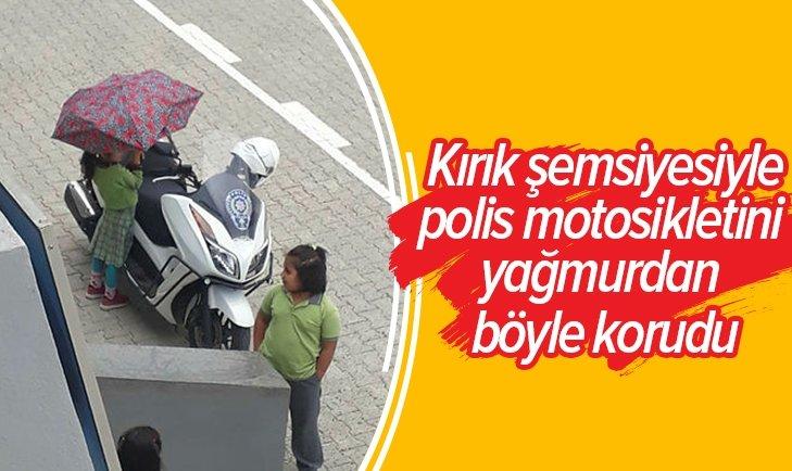 POLİSİN MOTOSİKLETİ ISLANMASIN DİYE ŞEMSİYEYLE BEKLEYEN KÜÇÜK KIZ